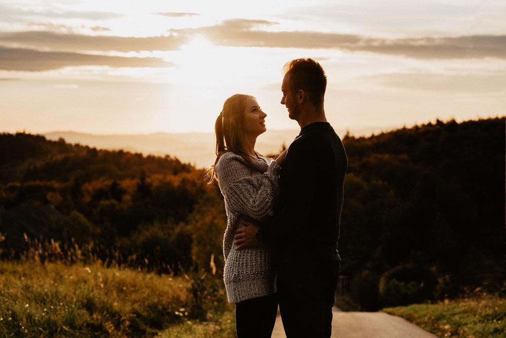 Kobieta i mężczyzna na drodze wtuleni w siebie.