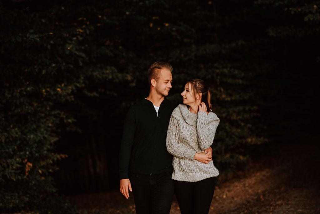 Kobieta i mężczyzna przy lesie są wtuleni.
