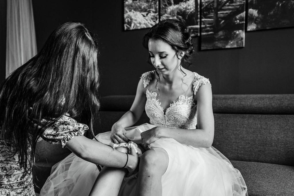 Ubieranie podwiązki na przygotowaniach do ślubu panny młodej