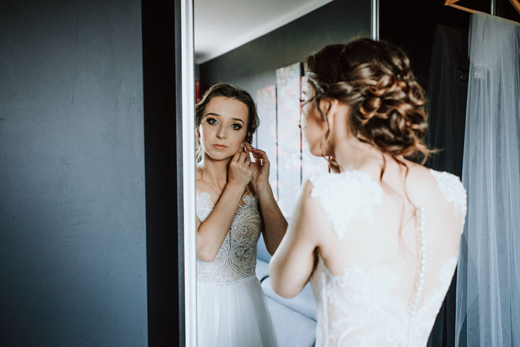 przygotowania do ślubu panny młodej zapinanie kolczyków przy szafie